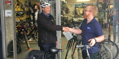 Eric Downey (left) receives the e-bike from Jake's Bikes